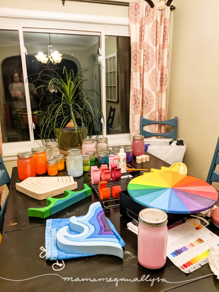 the dining room table covered in projects in the process of being painted