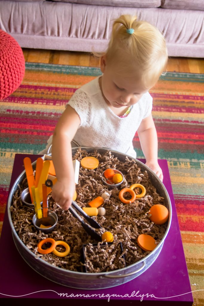 our Orange loose parts sensory bin is a simple setup but offers lots of different objects of different weights, sizes, and textures to practice picking up