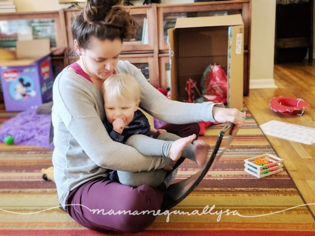 the wobble board or balance board is nothing more than a curve piece of wood. Yet it offers all kind of gross motor challenge in many different ways and its been so fun watching her learn new ways to play with it.
