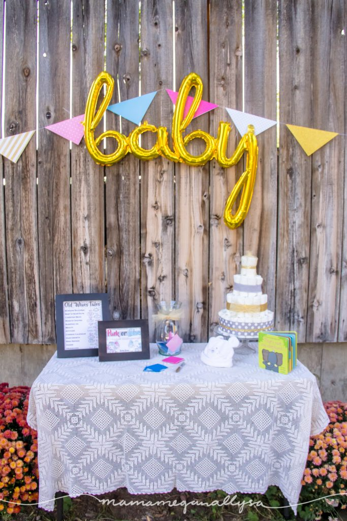 a vintage tablecloth and baby shower decorations including baby elephants and lots of pink and blue decor for our gender reveal party