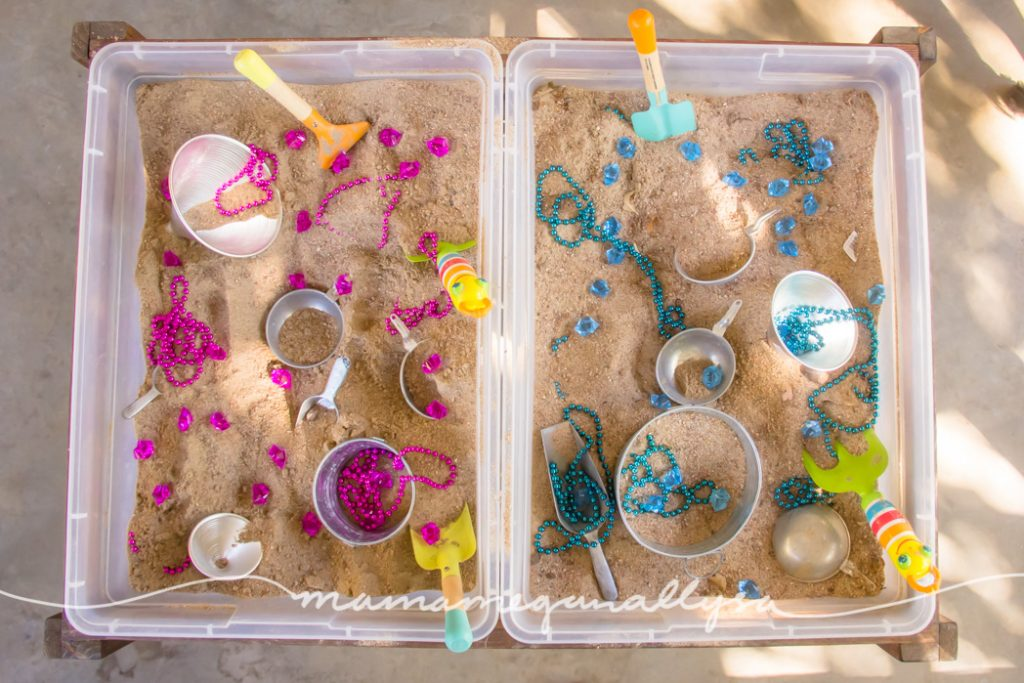 A two sided sensory bin in our sensory table for our gender reveal party. Filled with simple sand, scoops and buckets and lots of pink and blue treasures!