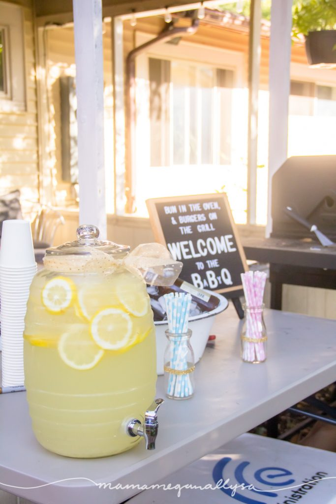 A dispenser of lemonade and some blue and pink paper straws in front of a letter board and the BBQ