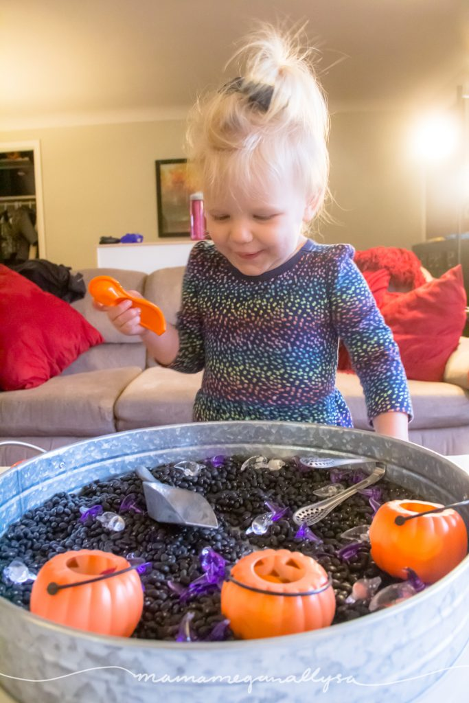 Having a good time exploring the loose parts in our Halloween Sensory bin