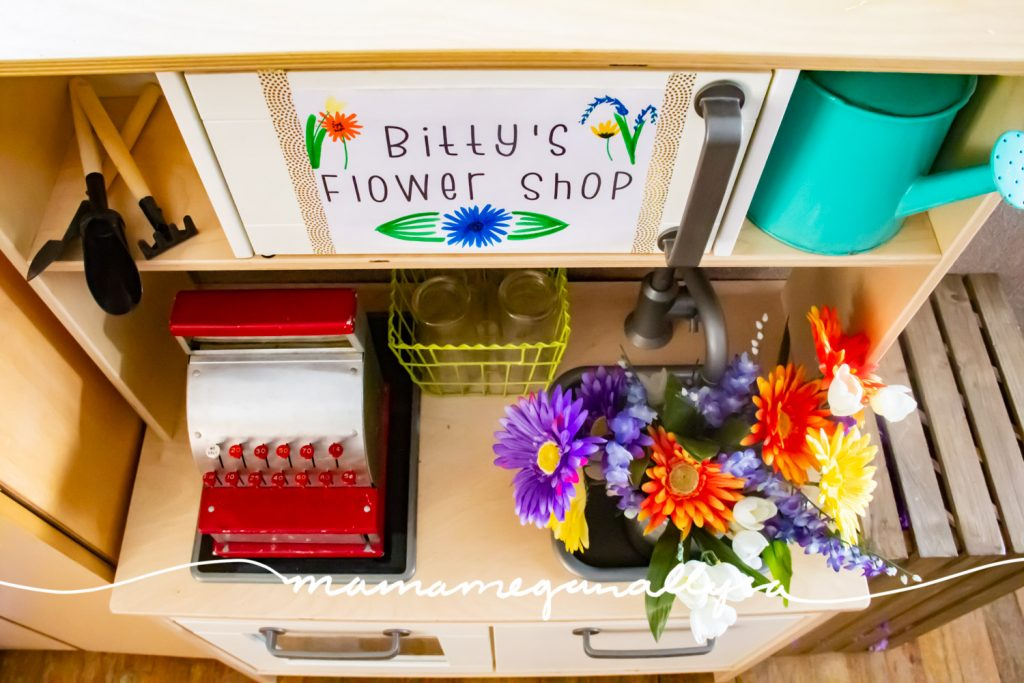I placed a cash register on the stove side of her play kitchen, added some small jars to arrange flowers in and a bucket of flowers. As additional themed items I included a watering can and some little shovels.