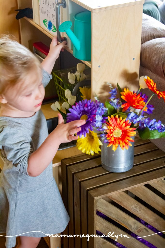 She really enjoys arranging and rearranging the fake flowers in our dramatic play flower shop