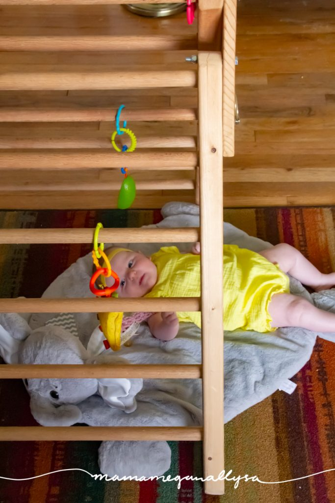 Our baby play space set up at 2 months is some dangle toys and a play mat under the Pikler triangle