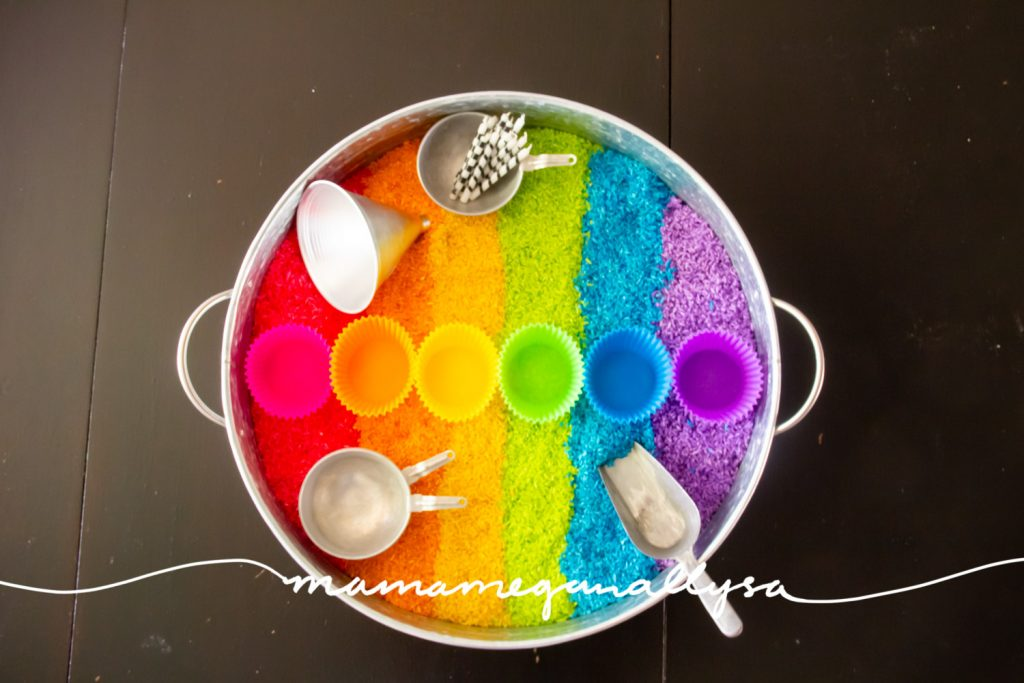 The tools in our rainbow rice sensory bin include a scoop and funnel for filling. Some mini pans and silicone cupcake liners for serving and some candles for posting