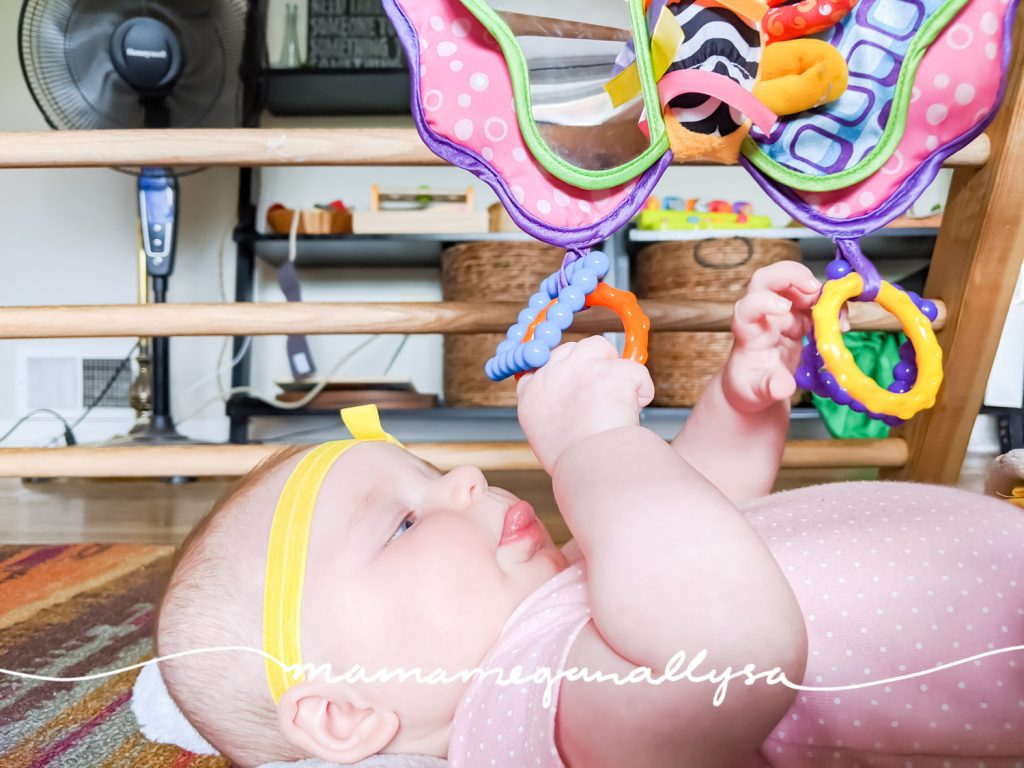 When your newborn begins to reach and grasp try hanging some toys down really low to make it easy for them to interact