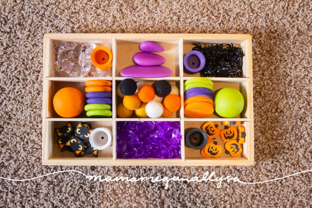 A tray filled will all sorts of goodies for the 3-year-old to play and design Halloween inspired creations, use for witches brew, and for anything her little head can think up! Loose parts are a completely open-ended play options that allows for creativity and imagination to grow