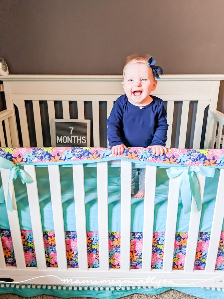 a baby girl standing in a crib with a letterboard that says 7 months
