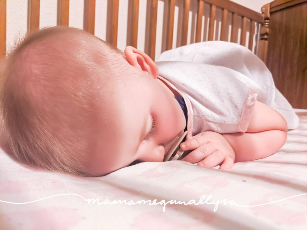 a close up of a baby with a pacifier asleep in a crib