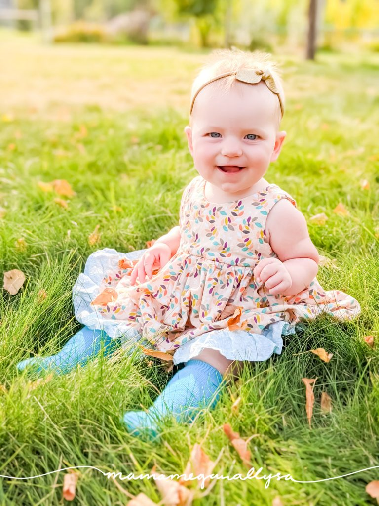 baby girl in a dress sitting in the grass surrounded my fall leaves