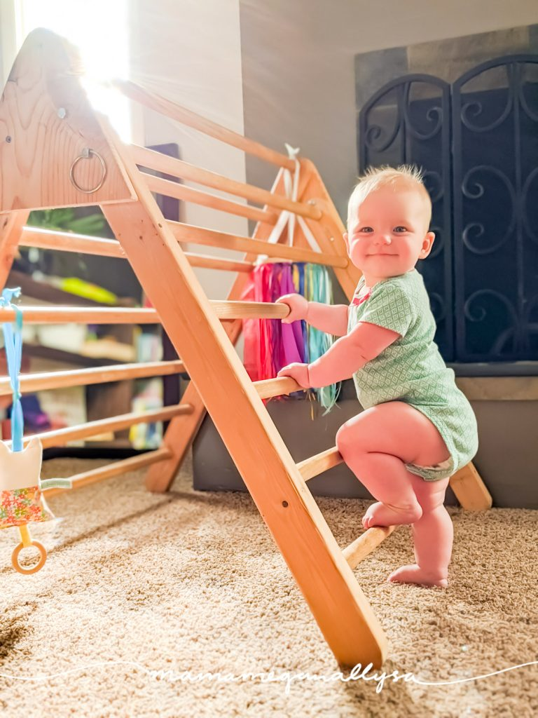 a baby with one foot up on a Pikler triangle (a wooden climbing toy shaped like a ladder folded in half)