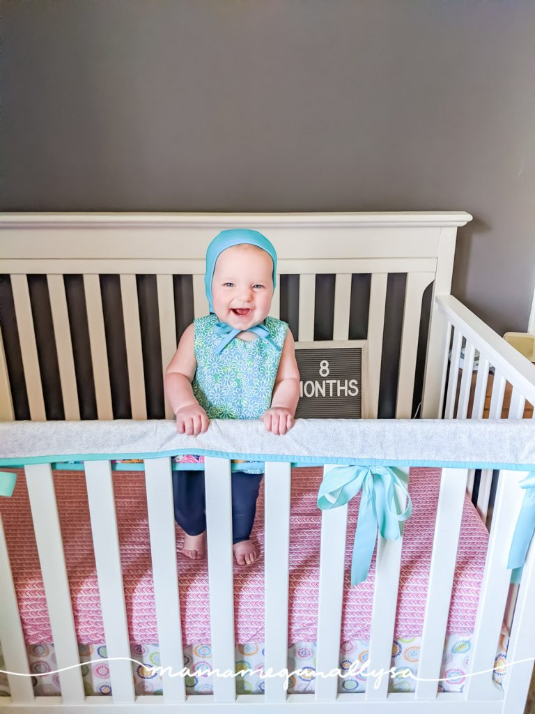 a baby girl standing in a crib with a letterboard that says 8 months