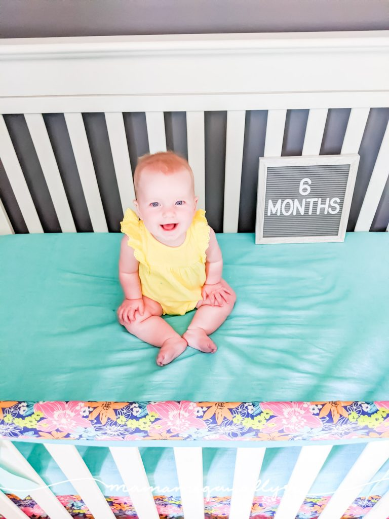 a baby girl sitting in a crib with a letterboard that says 6 months