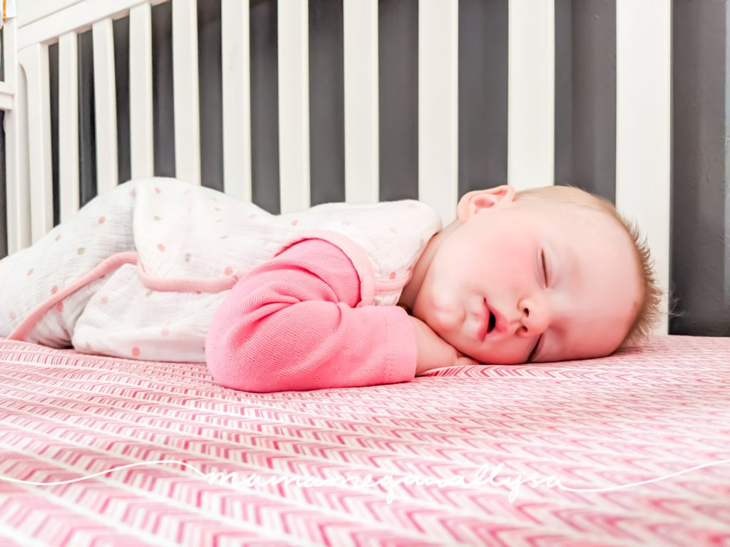 a close up of a baby girl fast sleep in her crib