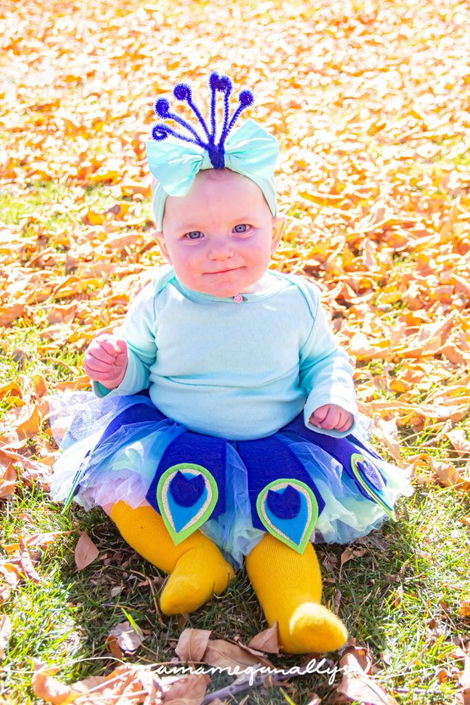 a baby dressed up like a homemade peacock costume for Halloween, sitting in the fall sunshine surrounded by leaves.