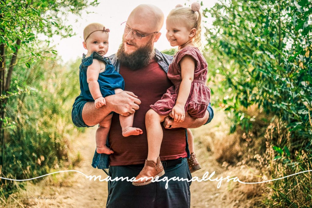 a daddy holding both his girls in his arms. He and the toddler are looking at the baby and the baby is looking at the camera
