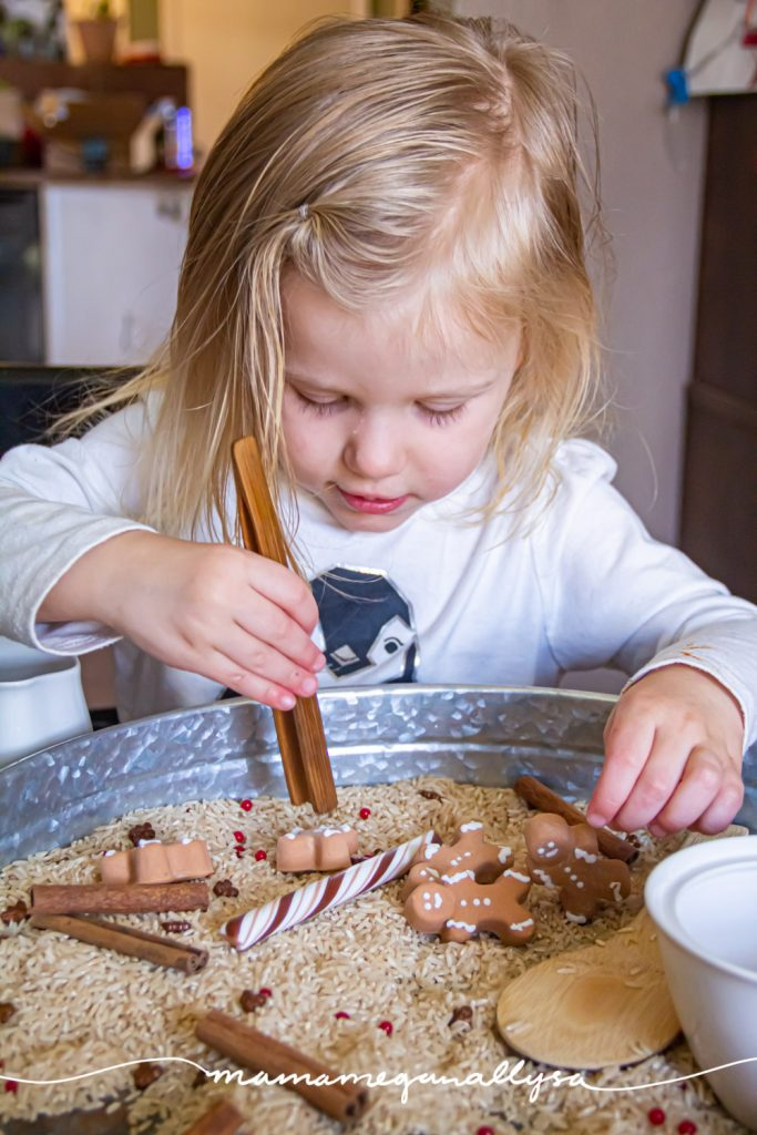 a toddler practicing with some wooden tongs in the gingerbread sensory bin