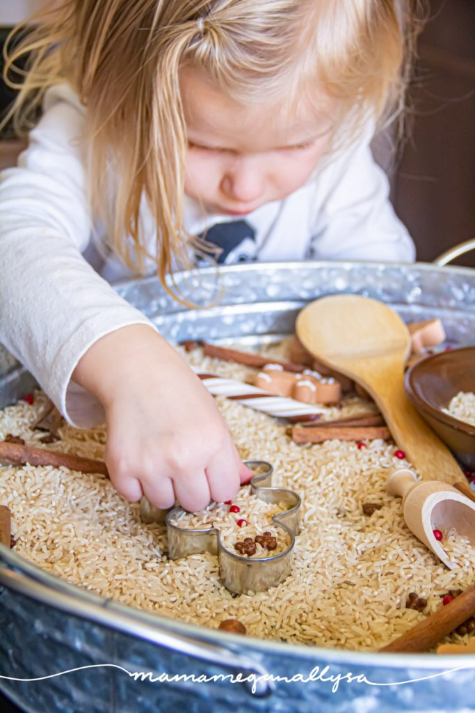 a toddler playing in a gingerbread sensory bin placing sprinkles as the buttons on a gingerbread man