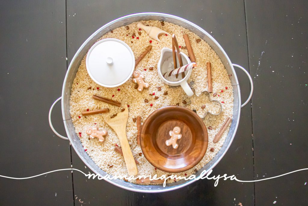an overview of the setup gingerbread sensory bin. with the cinnamon sticks, sprinkles, and gingerbread men all mixed into the rice and the tolls scattered around.