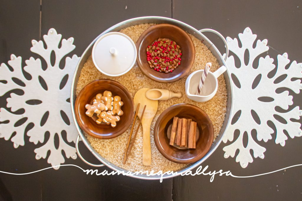 an overhead shot of the gingerbread sensory bin with three bowls of extras to add to the gingerbread rice. as well as three tools, and a sugar and creamer set for pouring