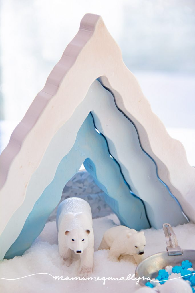 an arctic small world sensory bin filled with Epsom salt, a wooden ice cave stacker standing in the back of the tray with a mama polar bear and per cub stand in the shelter.