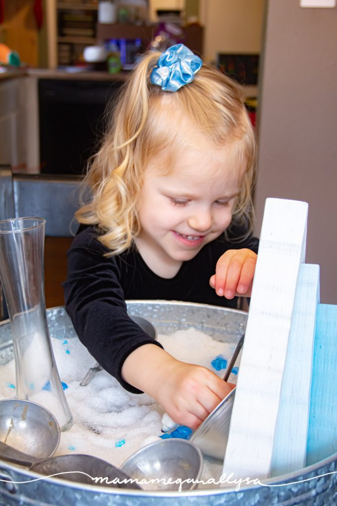 a toddler having fun and smiling while she plays with an arctic small world sensory bin