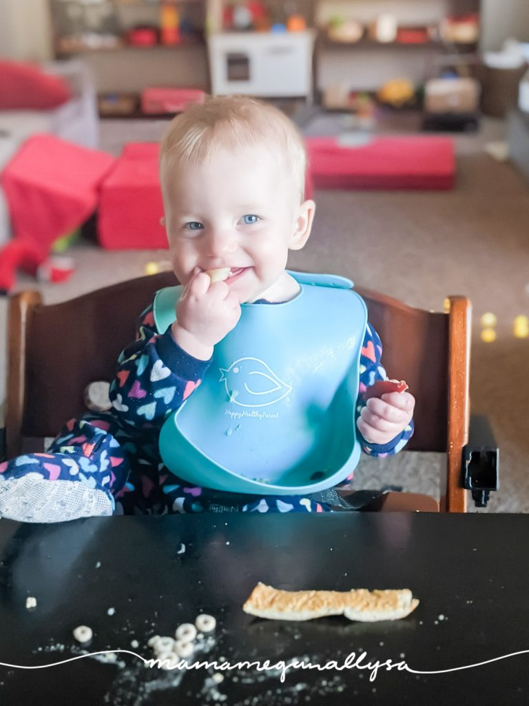a baby eating with one foot up on the table