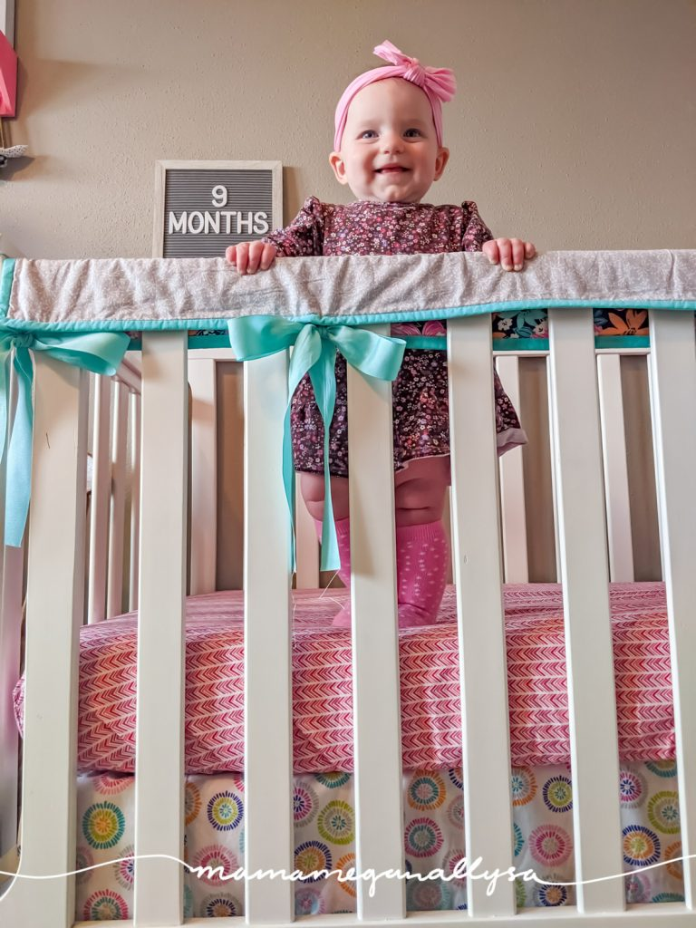 a baby girl standing in a crib with a letterboard that says 9 months
