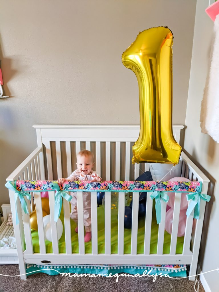 a baby girl standing in her crib that is filled with balloons and a big gold 1 balloon tired to the side