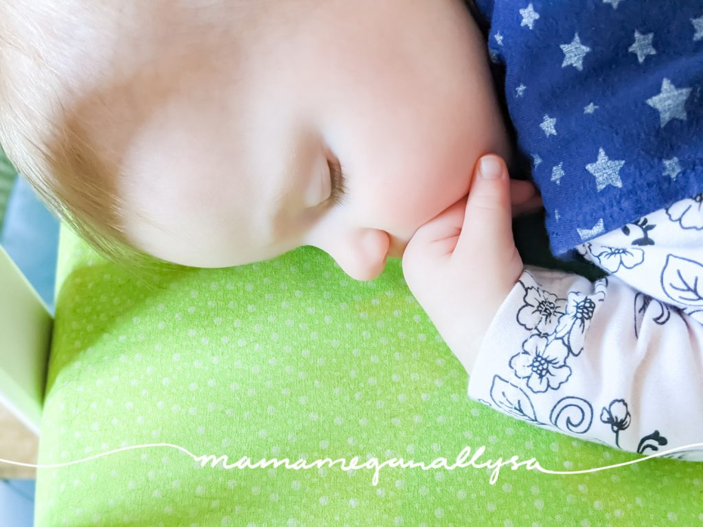 a baby sleeping with her hand tucked up by her face