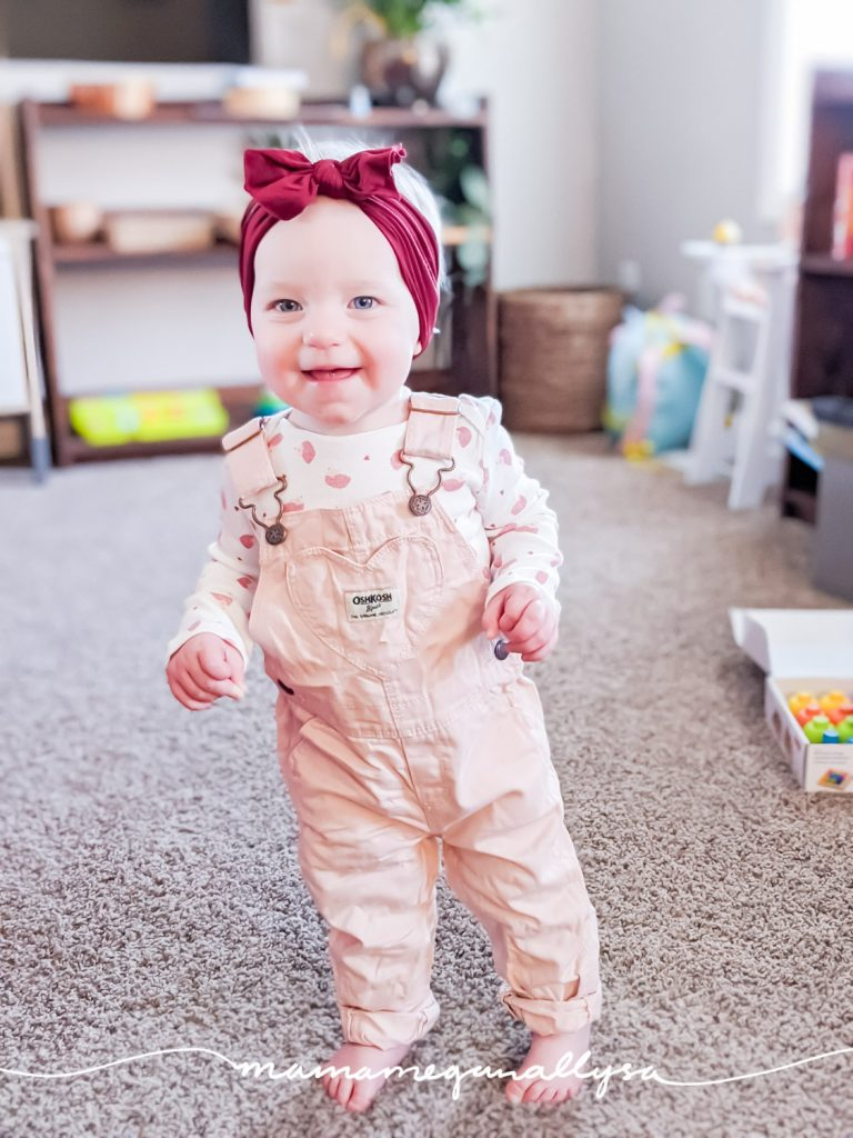 a baby stnading in pink overalls and a maroon headband