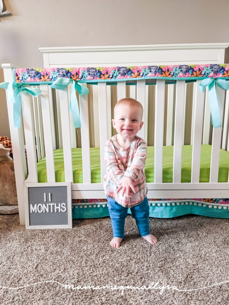 a baby girl standing in front of her crib with a letter board that says 11 months