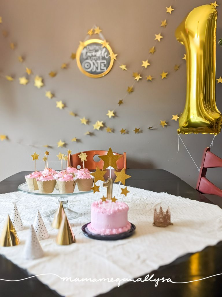 twinkle twinkle little one theme for a simple 1st birthday celebration at home with a pink smash cake and gold stars on top. gold star stands along the wall and a gold 1 balloon