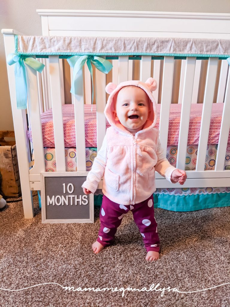 a baby girl standing in front of her crib with a letter board that says 10 months