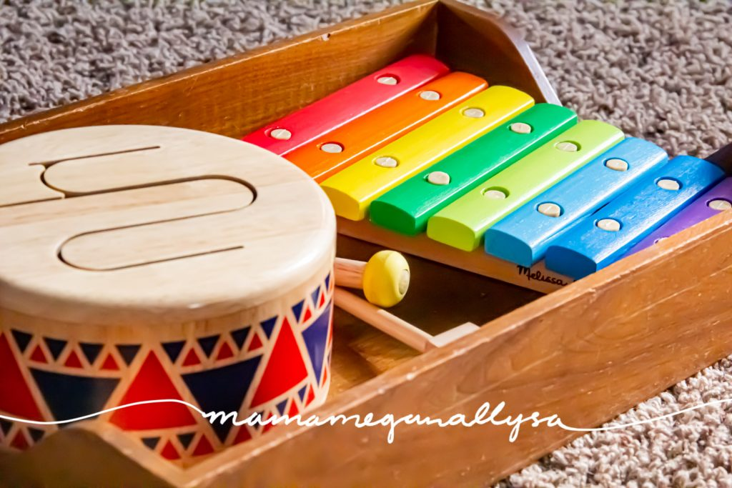 a close-up shot of a wooden toy drum and a wooden xylophone sitting in a wooden tray