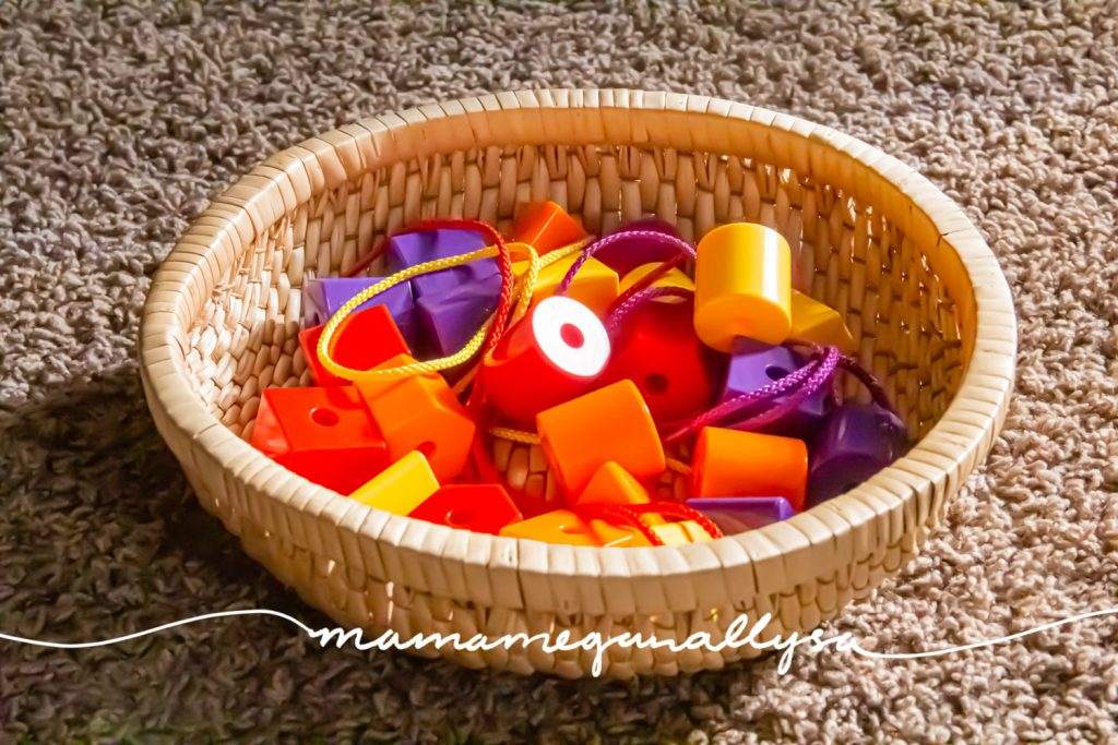 a close up of some plastic lacing beads and strings in a wicker basket