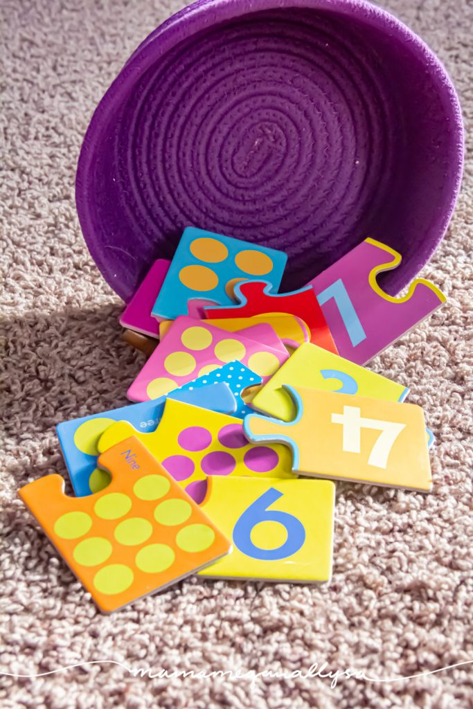 a set of 2 part jigsaw puzzles spilling out of a purple rope basket