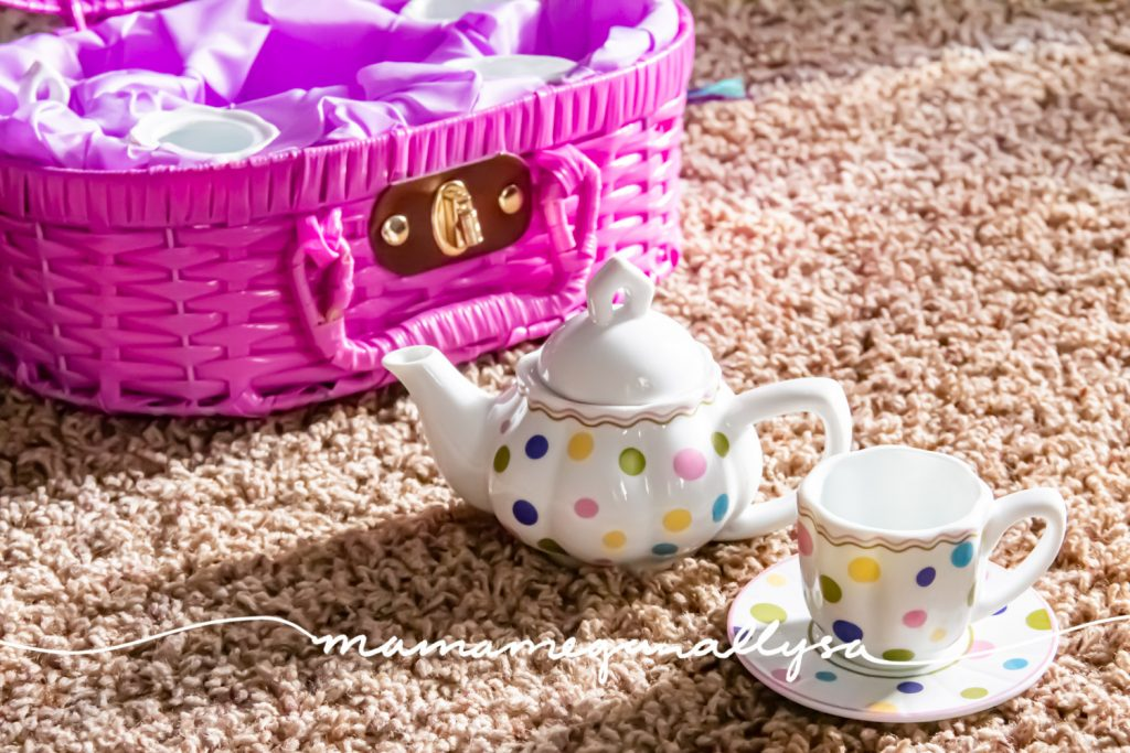 a close-up shot of a little kids polka dot porcelain teapot and cup on a saucer in front of a purple wicker carrying case
