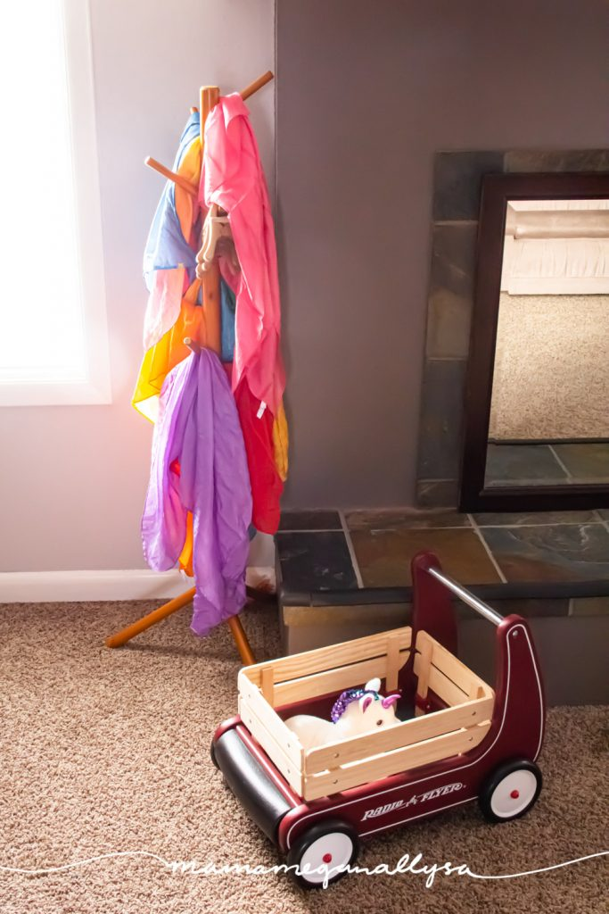our play silks hanging on a kids coat rack with the toddlers push wagon sitting in front
