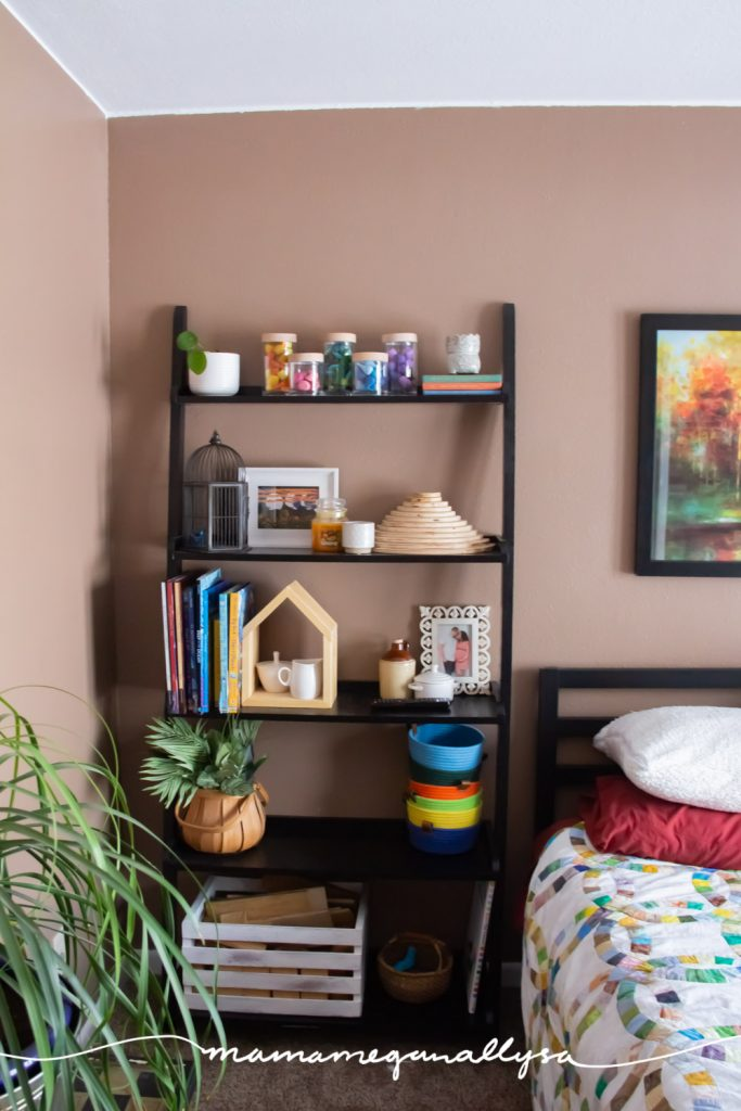 a tall black bookshelf in our guest room holding some of our loose parts, wooden blocks, books, and extra small world supplies