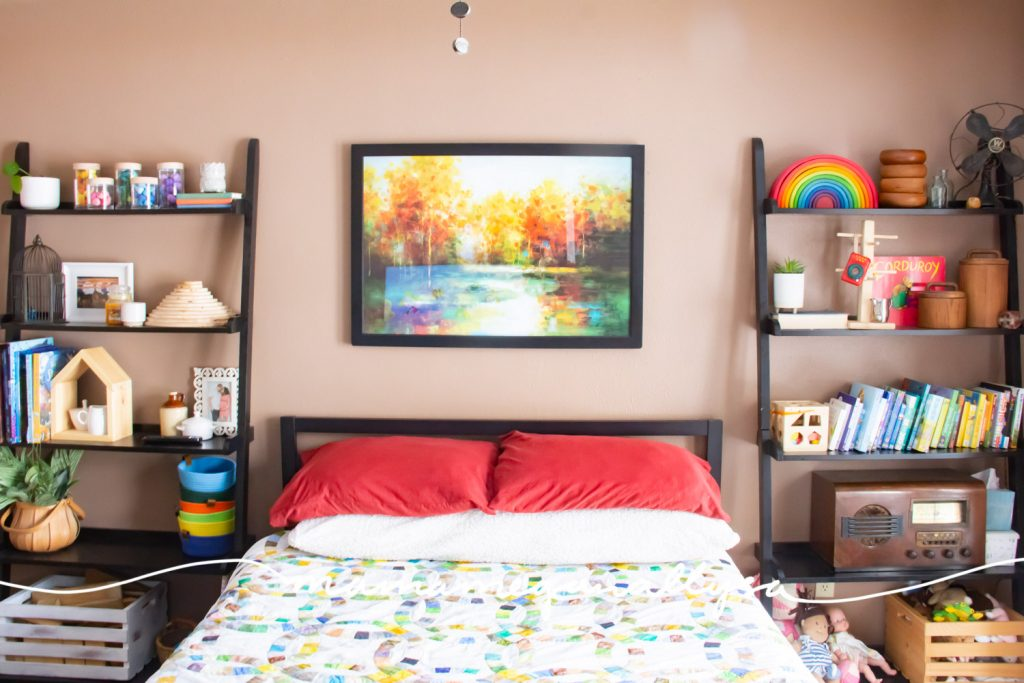 A guest room with tall bookshelves on either side of the bed with toys as well as general decor styled on the shelves