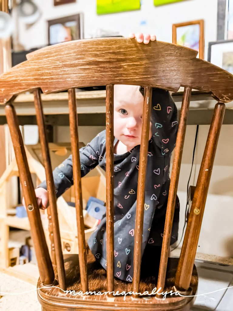 a little girl peeking through the back of a child sized wooden rocking chair