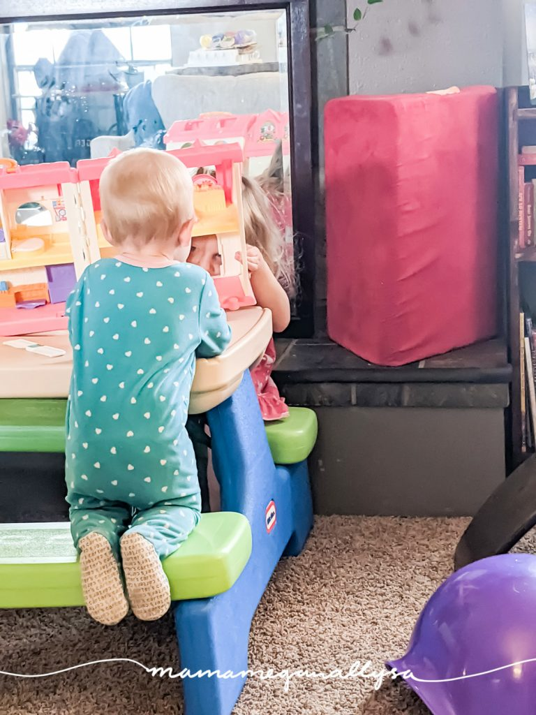 two little girls playing together in a livingroom