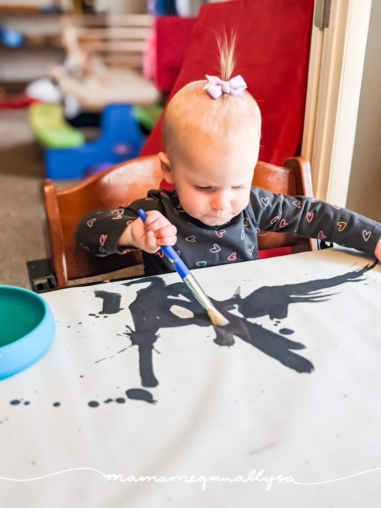 a little toddler using a caligraphy practice sheet to paint with water