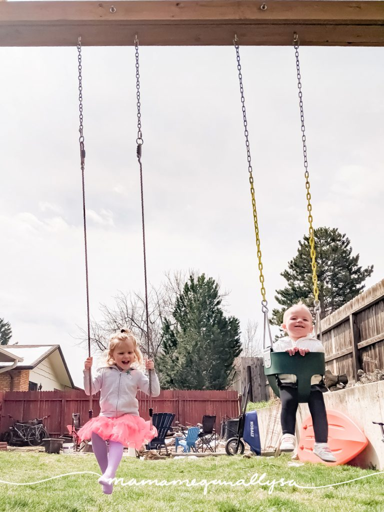 two little girls smiling and swinging in their backyard