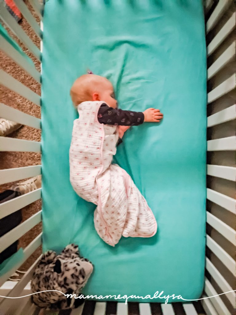 a baby asleep in her crib