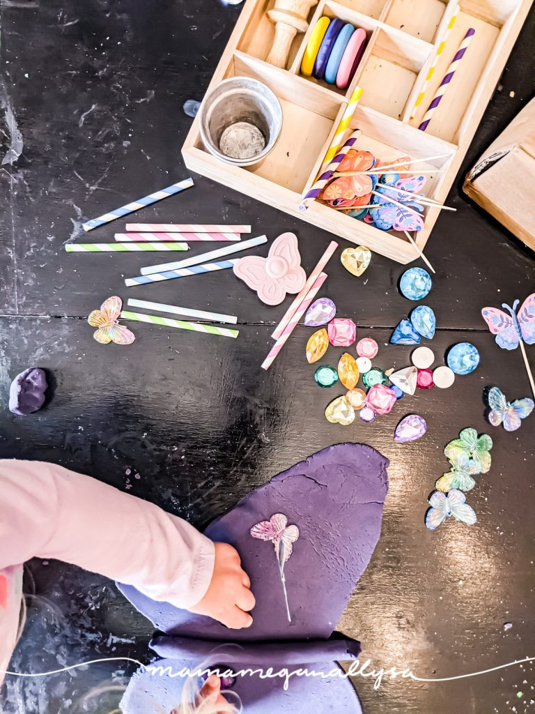 a top down shot of a child playing with a butterfly-themed play dough tray