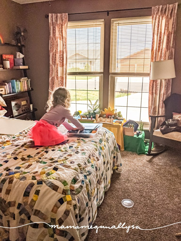 a little girl kneeling on a bed getting some toys out of a box